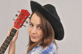 Portrait of a young twenty-year-old girl in a black hat , holding a red neck of a guitar from a person. — Stock Photo