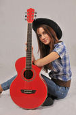 A smiling girl in a black hat, a plaid shirt, jeans and cowboy belt sits. Based elbow of his left hand on a red guitar, naklona to her head — Stock Photo