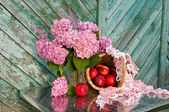 Still life with hydrangea and basket of nectarines on the old wooden wall background — Stock Photo