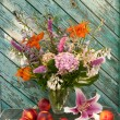 Stockfoto: Still life bouquet of hosta, astilbe, hemerocallis, pink hydrangeand nectarines. Nectarines and lily on table.