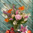 Still life bouquet of hosta, astilbe, hemerocallis, pink hydrangeand nectarines. Nectarines and lily on table. — Stock Photo #28659867