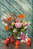 Still life bouquet of hosta, astilbe, hemerocallis, pink hydrangea and nectarines. Nectarines and lily on the table. — Stock Photo