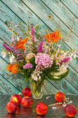 Still life bouquet: hosta, astilbe, hemerocallis, pink hydrangea and nectarines — Stock Photo