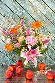 Still life bouquet of lily, hosta, astilbe, hemerocallis, pink hydrangea and nectarines. — Stock Photo