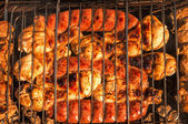Grilling chicken legs, small sausages and meat — Stock Photo