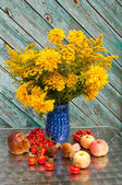 Yellow flowers bouquet in a blue vase with apples, mushrooms and rose-hips — Stock Photo