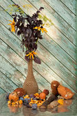 Basil, dill and cone flowers in a vintage vase with mushrooms still life — Stock Photo