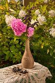 Natureza morta com hortênsia rosa em um vaso e branco planta hortênsia, como pano de fundo — Fotografia Stock