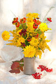 Yellow and orange flowers bouquet still life with berries and leaves — Stock Photo