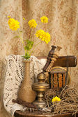 Still life with clockwork oil lamp and yellow flowers — Stock Photo
