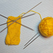 Knitting handwork with yellow needle ball and five knitting needles — Stock Photo #31868557