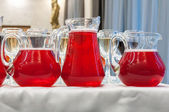 Three jugs with red juice on a white tablecloth with tall wine glasses — Stock Photo