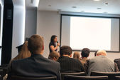 Business conference. people sitting rear and woman speaking at the screen — Stock Photo
