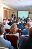 People sitting rear at the business conference and the speaker at the screen — Stockfoto