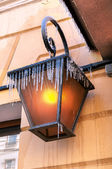 Ice-covered street lamp hanging on the building wall close up — Stock Photo