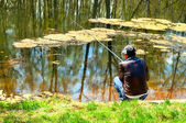 Fishman sitting at the river bank with the fishing rod rear view — ストック写真