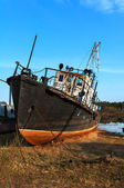 Broken rusty ship standing on the river bank — Foto de Stock