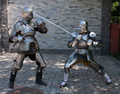 Two knights in the ancient metal armor standing near the stone wall — Stock Photo