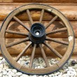Stock Photo: Old wagon wheel side by wooden wall