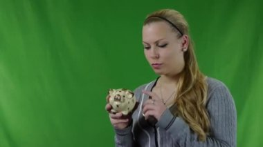 Happy Young Woman Putting Coin In Piggy bank against a green screen. No.02 — Stockvideo