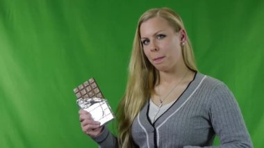 A young woman to tasting chocolate bar on green background — Video Stock