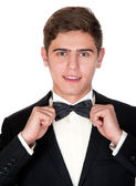 Cheerful man in a black suit adjusts his bow tie — Foto Stock