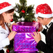 Young couple opens a gift on New Year's party — Foto de Stock