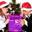 Young couple opens a gift on New Year's party — Stock Photo