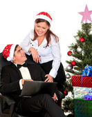 Ouple having fun looking into laptop near the Christmas tree — Stock Photo