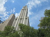 Woolworth building contra un cielo azul brillante visto desde city hall park en nueva york — Foto de Stock