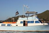 Torn Pirate Flag on Neglected Boat with Aqua Paint trim at Simpson Bay in St. Martin — Stock Photo
