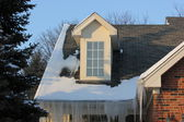 Icicles of winter hang from gutter or downspout of town homes — Stock Photo