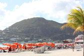 Colorful Bright Orange Beach Umbrellas and tourists enjoy Great Beach in Philipsburg, St. Maarten — Stock Photo