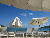 People getting a sun tan in with colorful beach umbrellas providing shade at Dawn Beach in St. Maarten — Stock Photo