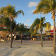 Boardwalk in Philipsburg, St. Maarten is lined with restaurants, bars, and tourists while sun set approaches — Stock Photo #43355711