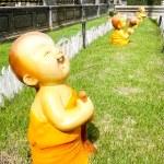 Kid monk mini figure acting on grass unusual — Stock Photo #39145081