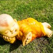 Stock Photo: Kid monk mini figure acting on grass unusual
