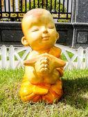 Kid monk mini figure acting on grass unusual — Stok fotoğraf