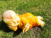 Kid monk mini figure acting on grass unusual — Stock Photo