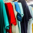 Dry colorful t-shirt and clothes in the air on hangers — Stock Photo