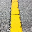 Stock Photo: Surface of asphalt road yellow line close up background