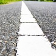 Surface of asphalt road white line close up background — Stock Photo #40894549