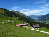Farm houses and distant view of Gstaad — Stock Photo