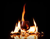 Bottle glass of cognac in fire flame on black background — Stok fotoğraf