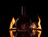Bottle and glass of wine in fire flame on black background — Foto Stock