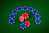 Chips for poker on green playing table — Stock Photo
