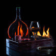 Bottle glass of cognac with poker markers and cigar in fire flam — Stock Photo