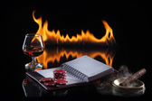 Glass of cognac with poker markers, notebook and cigar in fire f — Stock Photo