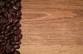Roasted coffee beans on wooden texture — Stock Photo