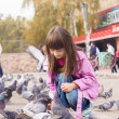 Small caucasigirl feeding pigeons — Stock Photo #35036473